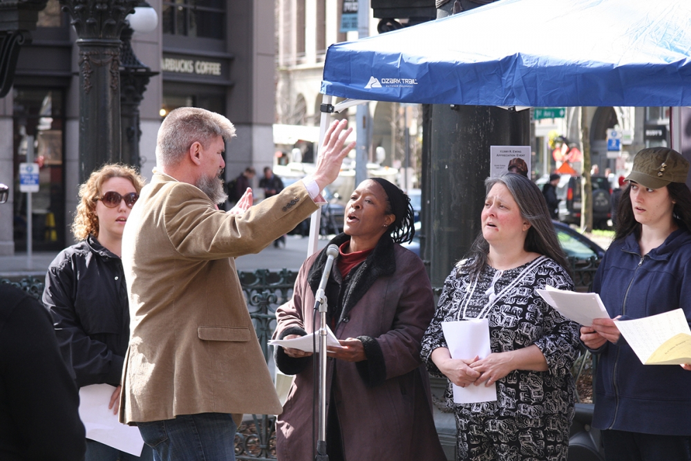 Sam Day leads a choir at the memorial for Ewing. Photo by Jon Williams, Real Change