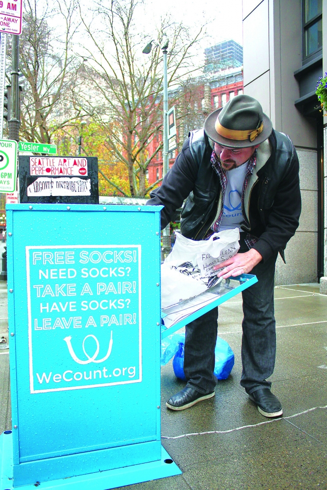 Graham Pruss drops off a bag of socks at the Pioneer Square sock box on First and Yesler. Photo by Jon Williams