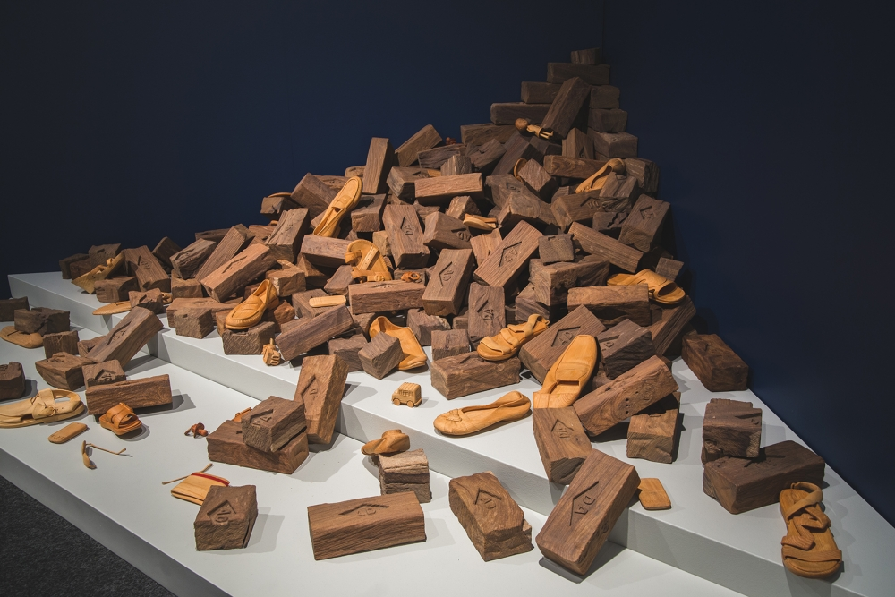 """The World is NOT Perfect,"" pine, mahogany and tulip wood, carved; red wood stain. The installation depicts the rubble from a decimated home. Photo by Matthew S. Browning"