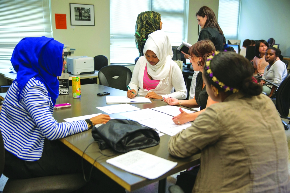 The Future Group discusses how to write narration. As the final of three sections, their group will predict what Yesler will be like in five to 10 years. Clockwise around the table from left: Filsan Abaisatar, Asma Adam, Claire Garoutte and Eva Gugsa.