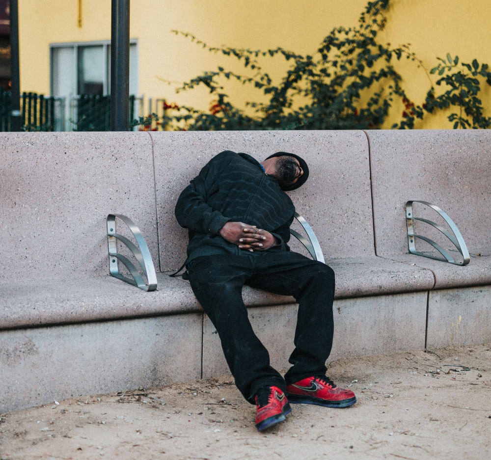 A homeless man tries to sleep on a hostile design bench in downtown LA. Photo by Tyler Nix on Unsplash