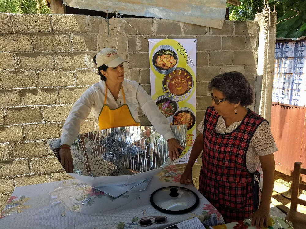 Lorena Harp, left, head of a project that promotes the use of solar cookers in Mexico, shows retired teacher Irma Jiménez how to assemble the device, in the poor neighborhood of Vicente Guerrero, Villa de Zaachila municipality, in the southwestern state o