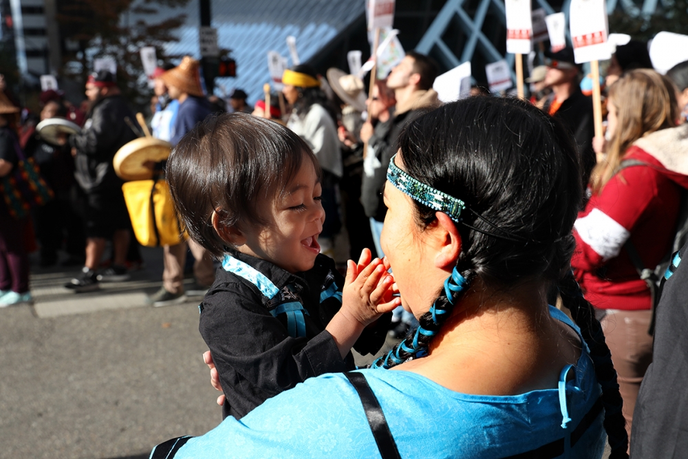 1-year-old Kennison Santo-Domingo plays with Kaleena Santo-Domingo along the march. The Santo-Domingos are from Okanogan Enrolled Colville tribe. Photo by Jon Williams