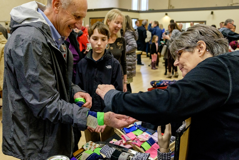 Susan shows how her cuff wallets work at St. Joseph Church in Seattle. Photo by Alex Bergstrom