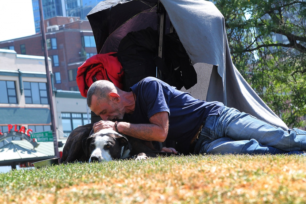 James Heitz comforts his dog during the heat of the day. Photo by Jon Williams