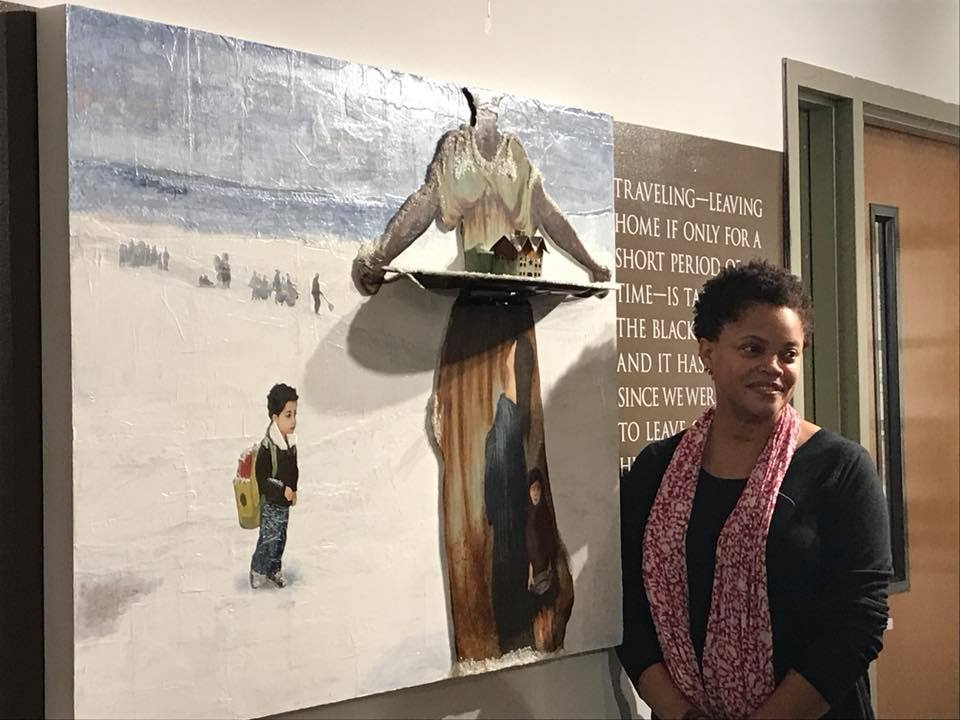 "Mixed-media artist Lisa Myers Bulmash stands in front of the collage ""Exposure"" during the opening of her NAAM show in November. Photo by Michael Lane"