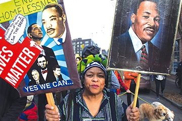 Fai Mathews of Seattle marches with her Martin Luther King Jr. signs. Photo by Wes Sauer