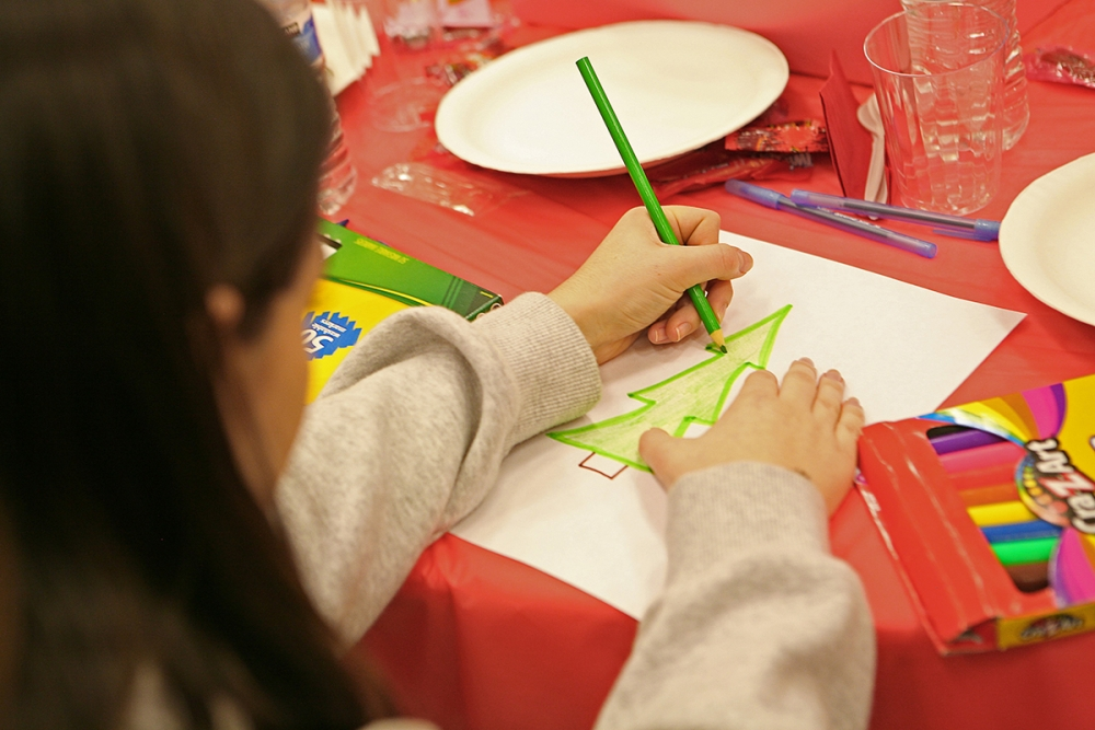 A child draws a christmas tree at the 2016 annual Holly Jolly Holiday Party. Photo by Joseph Romain