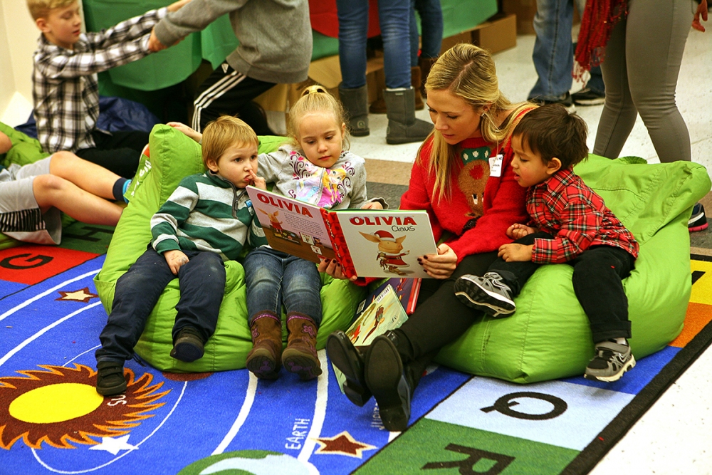 A volunteer reads a Christmas story to children at the 2016 annual Holly Jolly Holiday Party.
