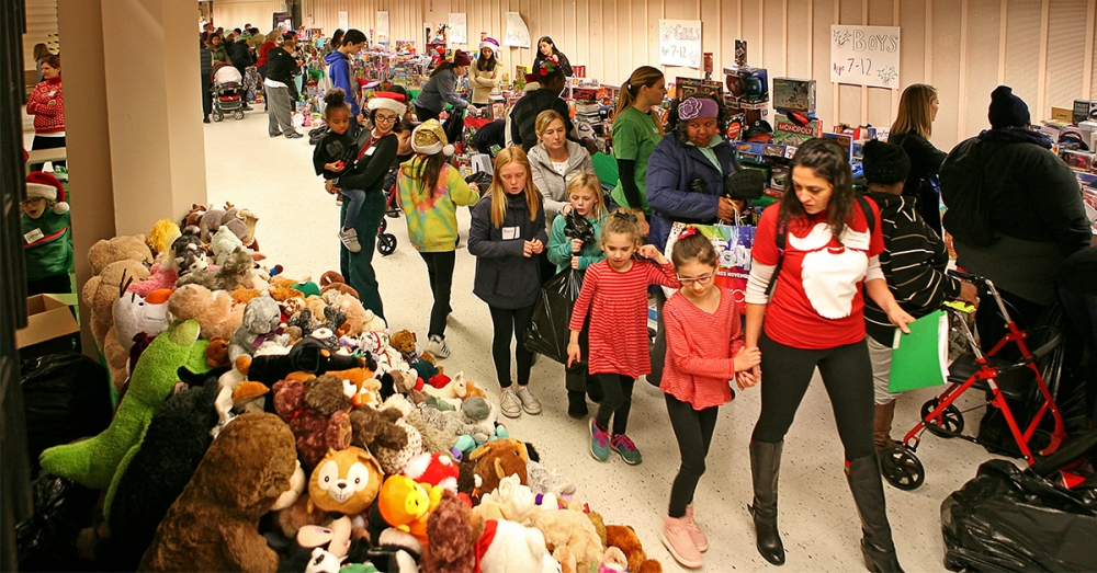 Volunteers help parents choose gifts for their children at the 2016 annual Holly Jolly Holiday Party for homeless individuals and families in Seattle. Hosted by Mary's Place.