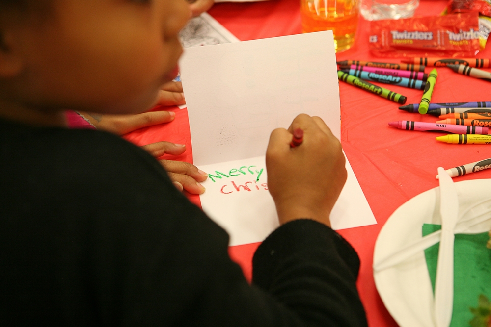 A child writes a Christmas card at the 2016 annual Holly Jolly Holiday Party. Photo by Joseph Romain
