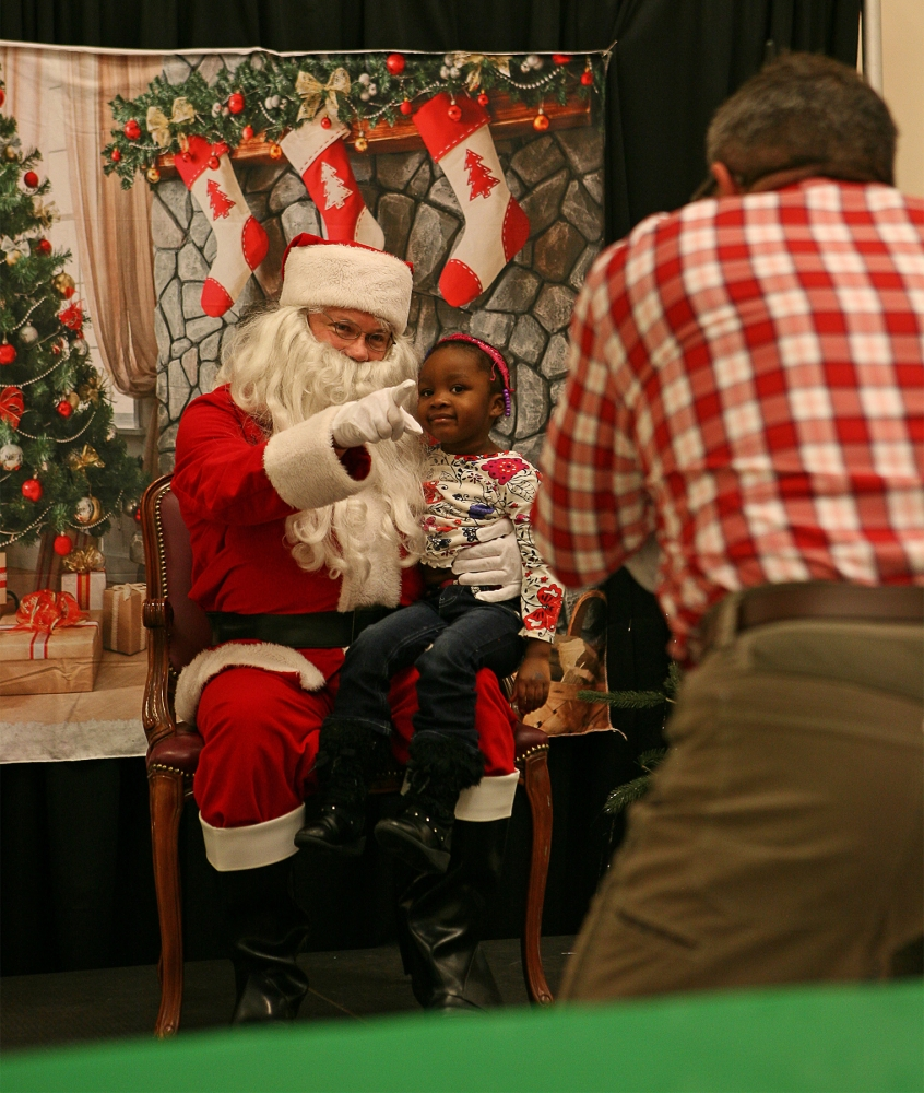 A child poses with Santa at the 2016 annual Holly Jolly Holiday Party. Photo by Joseph Romain
