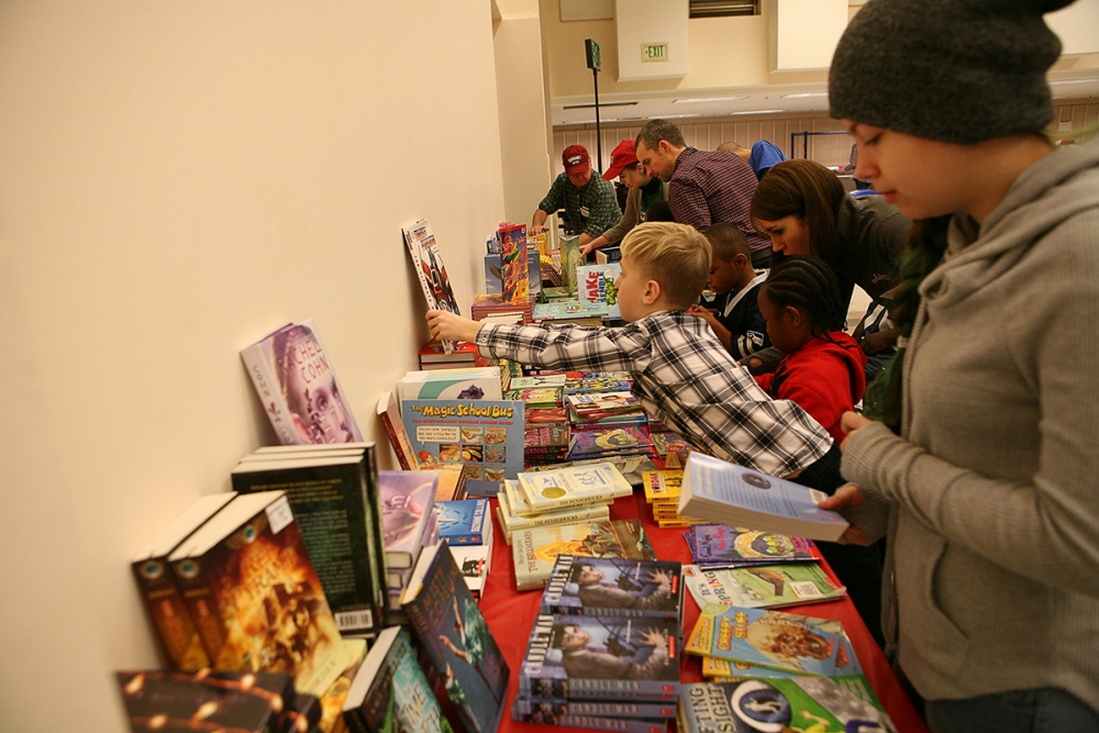 Volunteers help children choose books at 2016 annual Holly Jolly Holiday Party. Photo by Joseph Romain