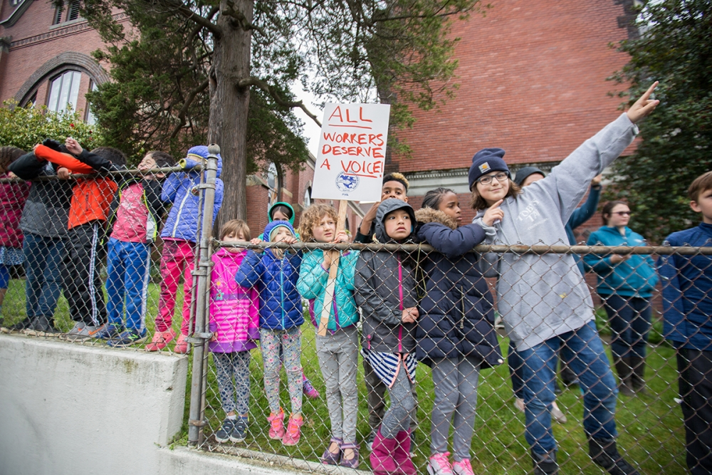 Children wave at participants in the March for Workers and Immigrant Rights. Photo by Alex Garland.