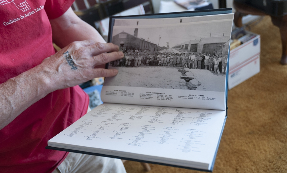 Mike Tagawa flips through the Minidoka internment camp yearbook. His right hand bears a tattoo of the number of the Idaho-based concentration camp for Japanese Americans. Photo by Monica Westlake