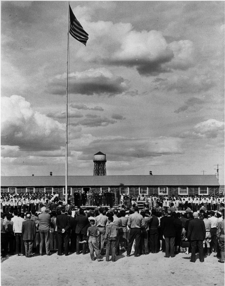Incarcerees gather around the American flag in the Minidoka concentration camp. Photo courtesy Wing Luke Museum collection.