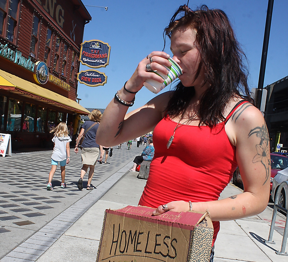 Orion Sackman takes a cool drink of water while flying a sign at the Seattle waterfront. Photo by Jon Williams
