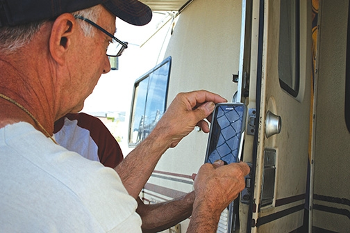Road to Housing Program Director Frank Scarabino snaps a photo of a vehicle resident's broken lock so he can find a replacement.
