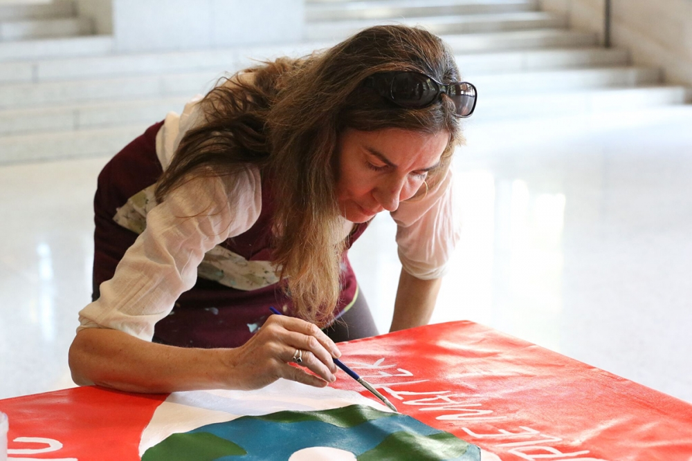 "Kelly Garland helps paint the ""We Are All Here"" group banner which was also displayed in Pioneer Square. Photo courtesy Path With Art"