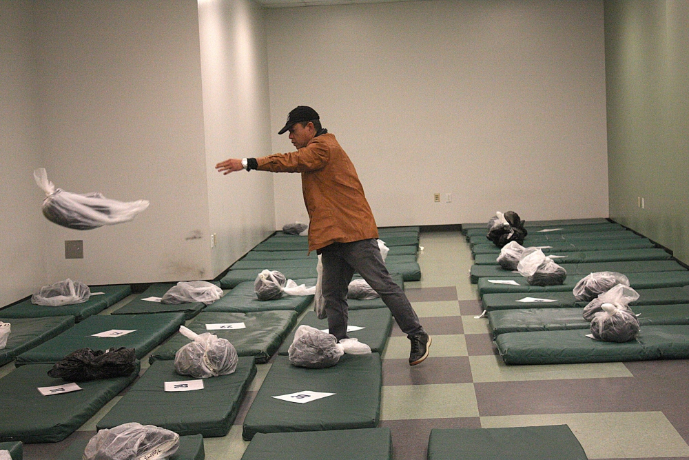 Vinh Nguyen throws a plastic bag containing a blanket on one of the  59 mats set aside for men in the City Hall shelter run by the Salvation Army.