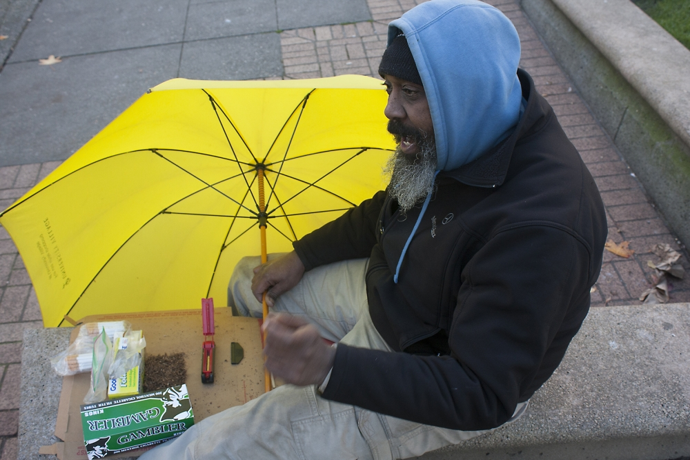 Rico rolls single cigarettes in Courthouse Park. Photo by Jon Williams