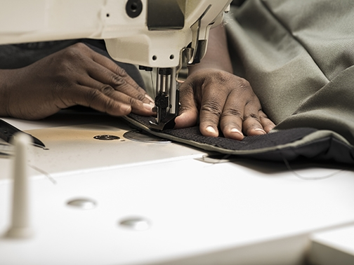 Woman sewing an EMPWR coat. Photo courtesy INSP