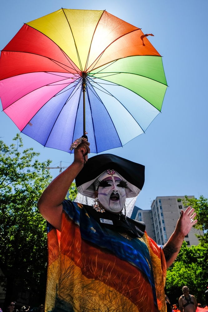 A member of the Sisters of Perpetual Indulgence sports a rainbow bumbershoot at the annual Seattle Pride Parade. Photo by Alex Bergstrom