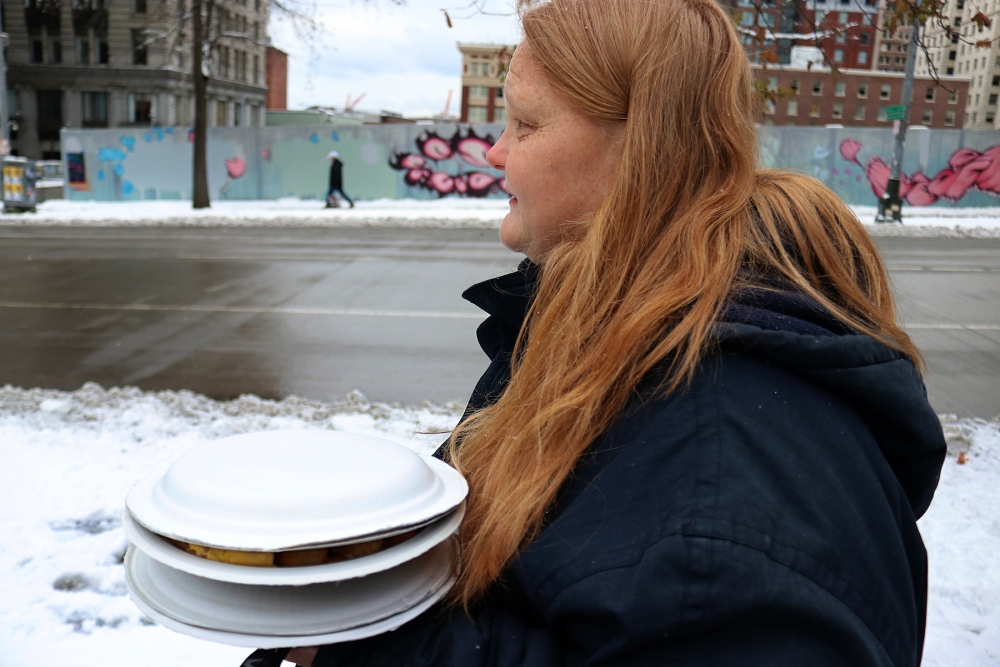 "Nicole Simper carries plates of food from Operation Sack Lunch's mid-day meal at Seattle City Hall. Simper has been staying at the City Hall shelter at night and at the Salvation Army day shelter, ""I'm usually staying outside,"" she said. ""But it's been so"