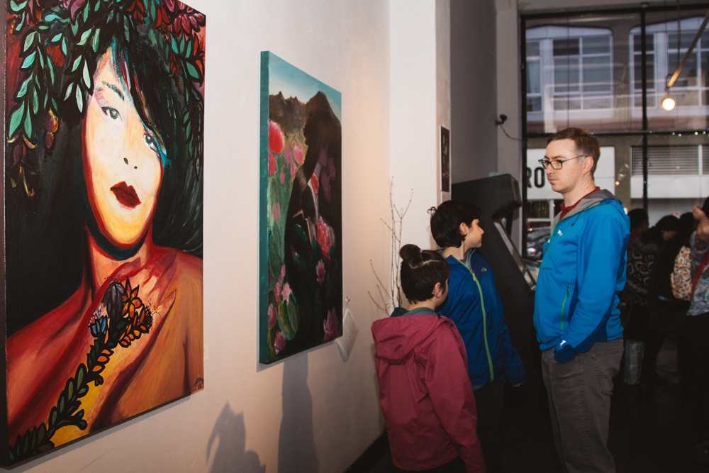 A visitor to Vermillion views Zaka'an's self-portraits at Vermillion on opening night. Photo by Leo Carmona