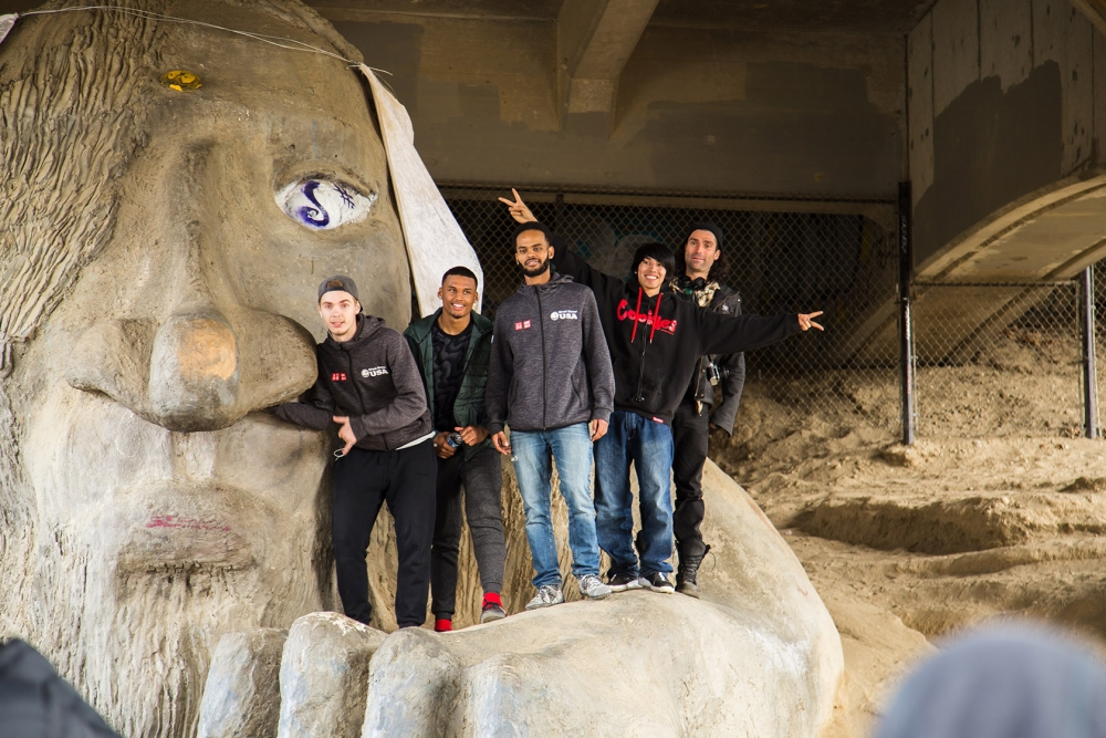 Players scaled the Fremont Troll in a bit of sightseeing before heading off to play some soccer. Photo by Matthew S. Browning