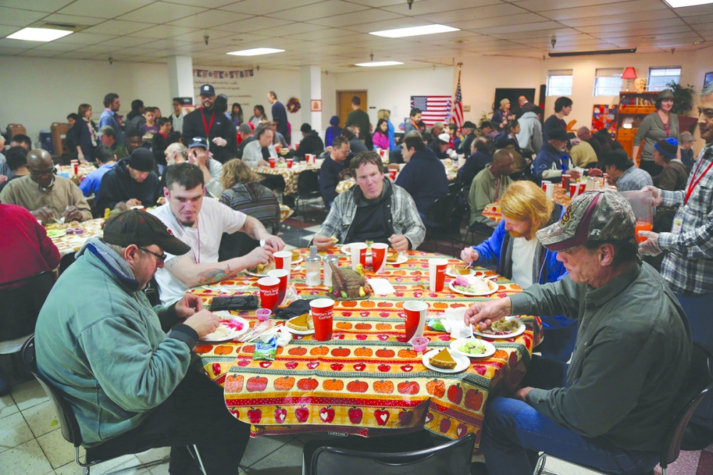 A full house of those enjoying a hot meal on Thanksgiving and the volunteers who are serving them at The Salvation Army. Photo by Ted Mase