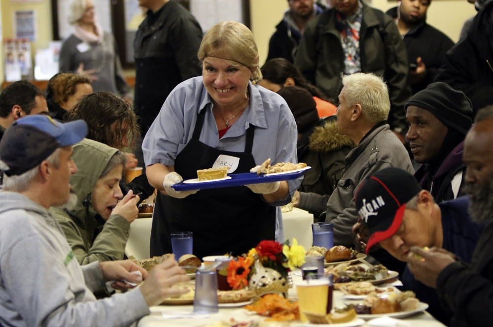 Mary Sanford, of Seattle, serves up Thanksgiving meals with a smile to those residents and guests who came to the Millionair Club  to celebrate the holiday.
