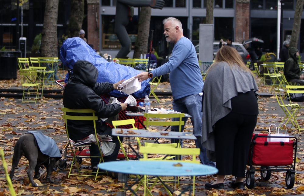 In Occidental Park, Andy and Carri Johnson, of Seattle, hand out one of the 45 turkey sandwiches and drinks — as well as  dog treats — they make for those in need on Thanksgiving day. The couple said they just felt like giving back.