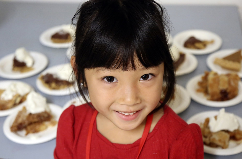 Nathaly Saelee, 5, of Burien, helps out at The Salvation Army. Saelee and her family served meals to the residents and others who stopped by on Thanksgiving.