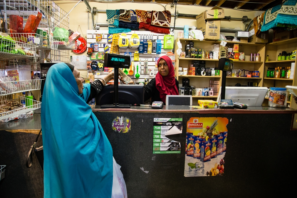 Mariam Abdi, a clerk at the Fresh and Green Produce Market, gives change to a customer. The Market specializes in goods for the East African community that are difficult to find elsewhere. The store could close if the city of Tukwila takes over the proper