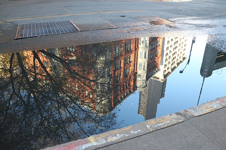 Reflective puddle in Pioneer Square including Smith Tower taken in the Seattle Street Lens program.