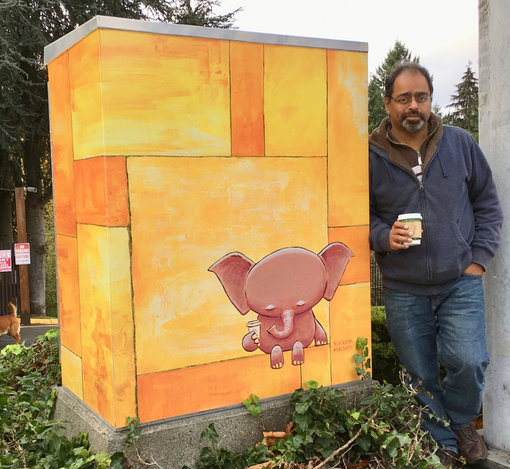 Artist Vikram Madan stands next to a utility box wrap based on 'Contemplation, In Yellow' at the intersection of 122nd and Ambaum in Burien. Photo courtesy Madan.
