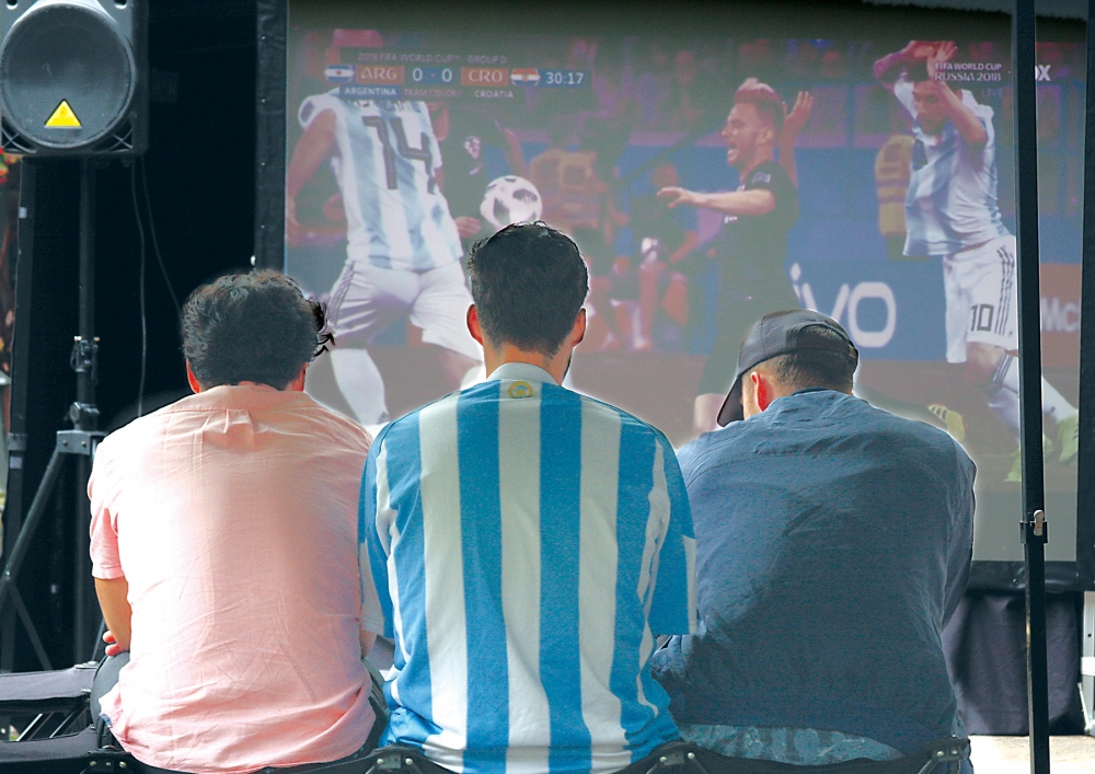 Juan Espi, left, Nick Richardson — in the Argentina jersey — and Mathew Cert met up in Occidental Park to watch the giant screen that broadcast the Argentina Vs. Croatia football match Thursday, June 21, during the World Cup. Photo by Jon Williams