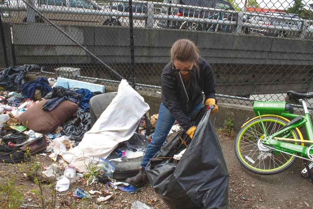 Cindy Hohlbein picks up trash along Interstate 5 near the Yesler Way overpass. Photo by Dave Parish