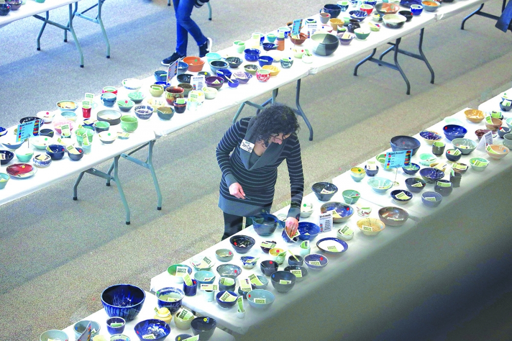 Pierce County potter Jen Davis checks one of her bowls. She has contributed for 15 years.