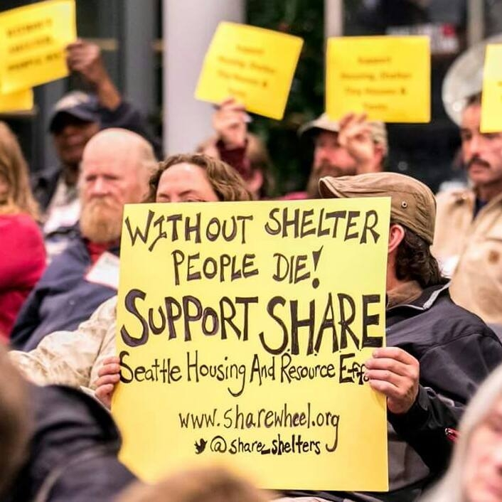 Protesters represent share/wheel at a 2015 rally in Seattle. The housing communities organize continuous activism and support for anti-homelessness policy. Photo courtesy of SHARE/WHEEL