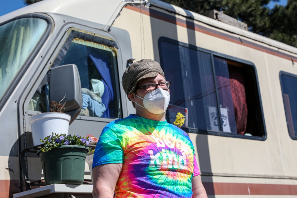 Powers poses for a photo in front of their RV. Currently, Powers parks their RV on a strip of property that is privately owned after coming to an agreement with the landlord. This is not Powers' first time being unhoused. They have tried for the Section 8