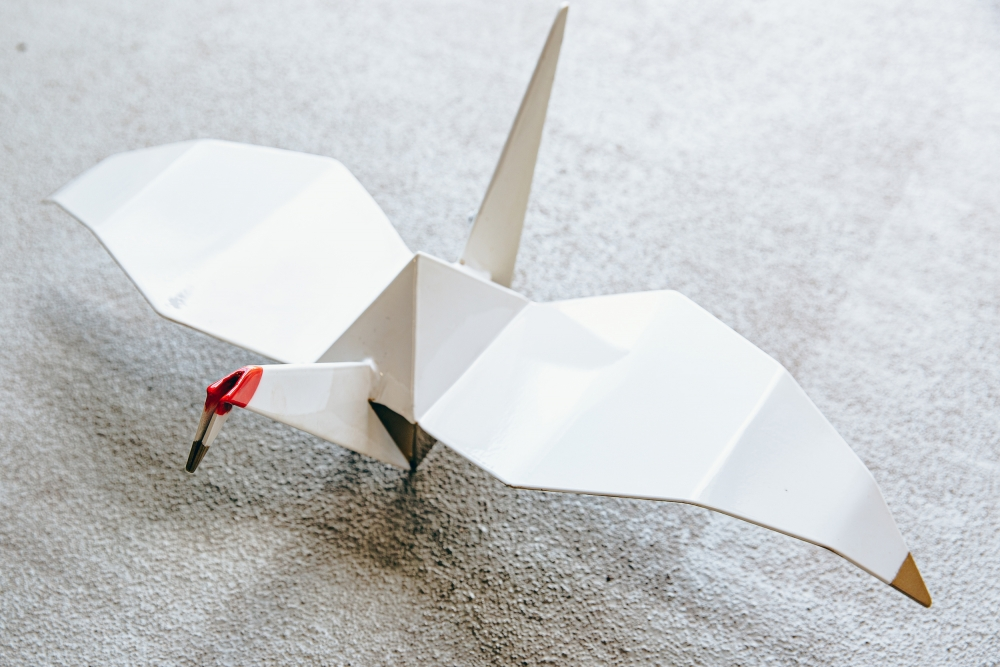 """Chinn crafted dozens of lightweight origami-style birds out of stainless steel, above, to cover the 18-foot-high sculpture """"Returning Home."""""""