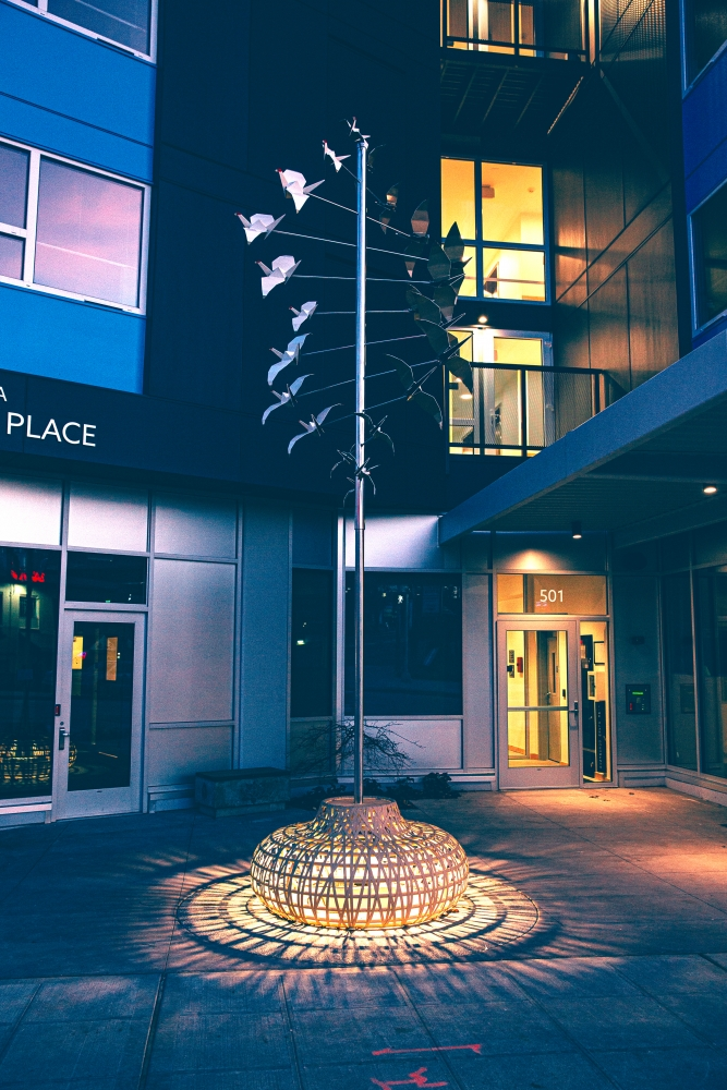 """His stainless steel sculpture """"Returning Home,"""" outside of the Plymouth Housing Building in Chinatown-International District, gently shifts in the wind and includes lighted seating."""