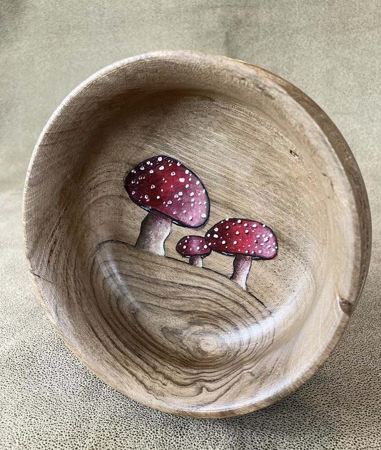 Anni and John Furniss found each other through making their unique art. Their collaboration grows, as Anni has begun painting with acrylic on wood plates crafted by John, like these mushrooms.