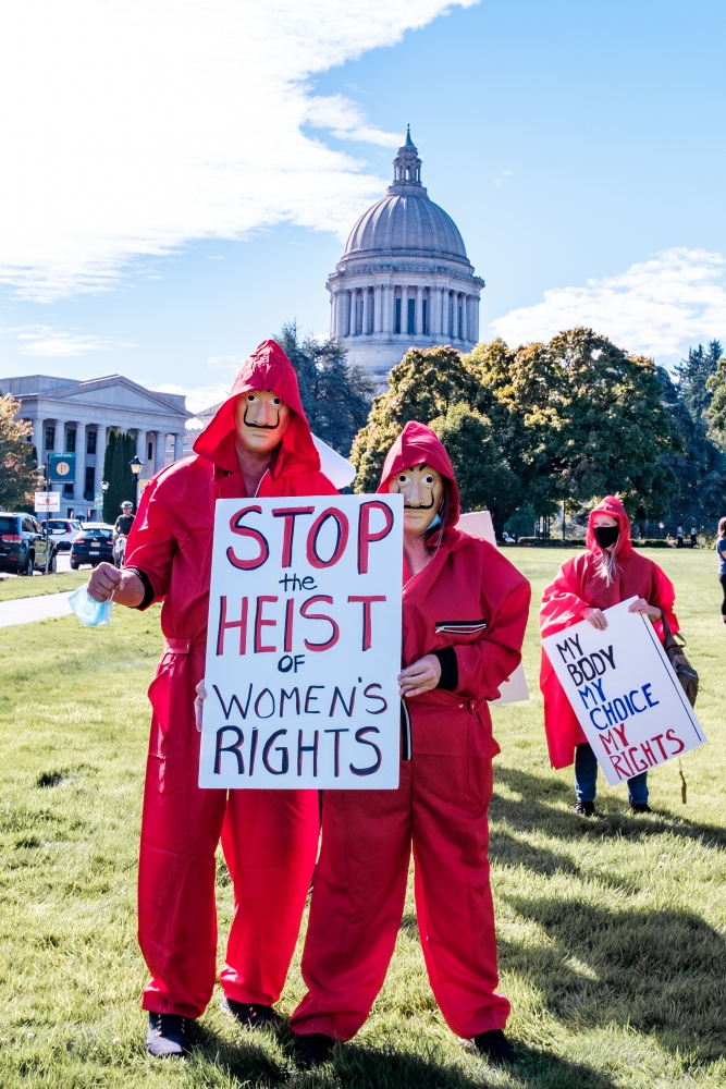 """Protesters in Olympia hold signs against hate and in defense of women's rights, including one modeled after the Spanish show """"Money Heist."""""""