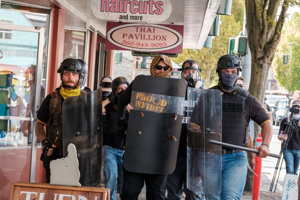 Members of the hate group hold riot shields as they advance alongside an Olympia sidewalk; Toese appears again, on the far right.